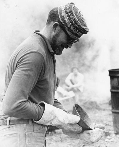 An image of John Tuska inspecting a raku fired clay bowl