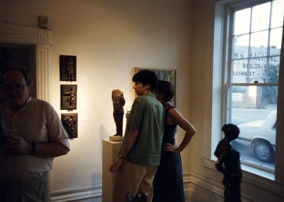 A image of John Tuska, Debra Hensley and an unidentified person viewing artwork at the Heike Pickett Gallery