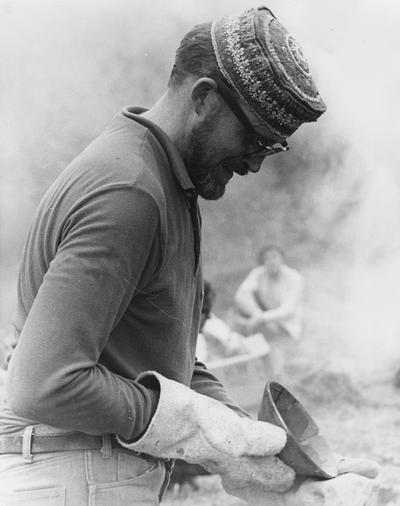 John Tuska examining a clay vessel after a raku firing