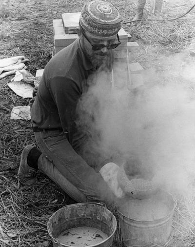 John Tuska cooling a clay vessel after a raku firing