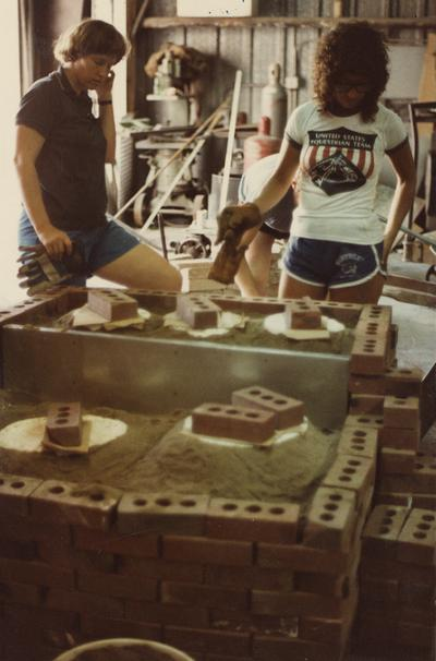 Three students preparing molds for a foundry class at the University of Kentucky. The photograph was taken by Ted Bronda