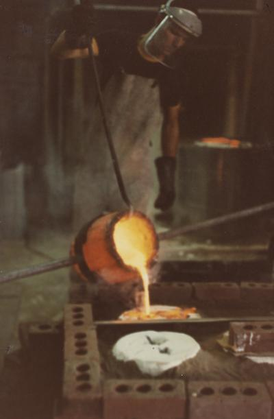 An unidentified person assisting with a pour for a cast at the University of Kentucky foundry. The photograph was taken by Ted Bronda