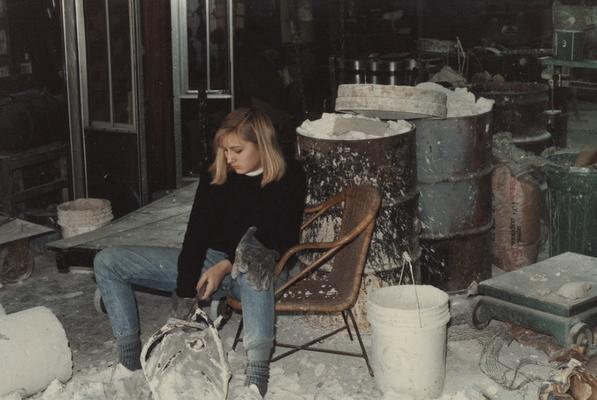 An unidentified student breaking apart a mold in the University of Kentucky foundry. The photograph was taken by Zig Gierlach